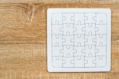 Blank jigsaw puzzle on wooden table Royalty Free Stock Photos