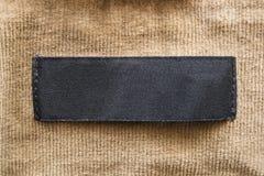Blank label. Blank black label on beige velvet cloth stock photography