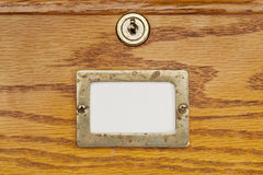 Blank label of file cabinet drawer. Blank label in brass holder on a wooden file cabinet drawer with a lock Stock Photos