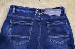 Blank label on gray denim pants - new clothes stock photo