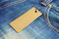 Blank label price tag mockup on blue jeans. royalty free stock photography