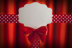 Blank label, ribbon and bow on red background Royalty Free Stock Photos