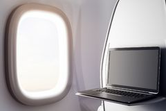 Blank laptop in airplane. Close up of laptop with blank screen next to airplane window. Freelance concept. Mock up, 3D Rendering Royalty Free Stock Images