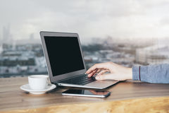 Blank laptop with hand. Hand typing on blank laptop keyboard with blurry city in the background. Mock up Royalty Free Stock Image