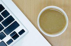 Blank laptop keyboard with coffee paper cup on wooden desk Royalty Free Stock Photos