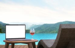 Blank laptop monitor and poo lbed 3d rendering image. An empty laptop screen is placed on a table by the pool. focus at laptop monitor. There are mountain and Stock Photos