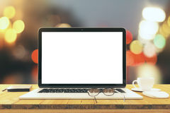 Blank laptop screen on wooden table with eyeglasses and cup of c Royalty Free Stock Photos