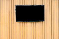 Blank lcd Flat screen television hanging at the wooden wall. Blank lcd Flat screen television hanging at the planks wooden wall Stock Image
