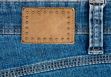 Blank leather jeans label decorated by rivets Stock Photography