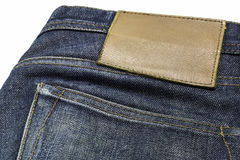 Blank leather jeans label sewed on a blue jeans. Stock Photos