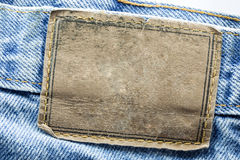 Blank leather jeans label. Sewed on a blue jeans  on white background Stock Photos