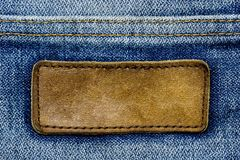 Blank leather label blue jeans. Blank brown leather label on vintage blue jeans. Suitable for backgrounds, articles about fashion clothing stock images