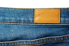 Blank leather label on blue jeans  on white Stock Photos