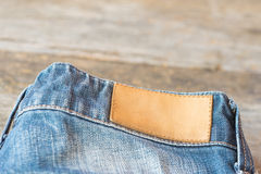 Blank leather label blue jeans on wooden background. Royalty Free Stock Photo
