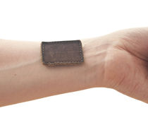 Blank leather label sewed on a hand Stock Image