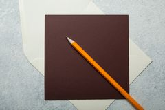 Blank letterhead and orange pencil on white vintage background.  royalty free stock photography