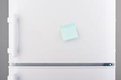 Blank light blue sticky paper note on white refrigerator Stock Photo