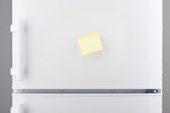 Blank light yellow sticky paper note on white refrigerator. Door stock photography