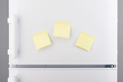 Blank light yellow sticky paper notes on white refrigerator Stock Photography