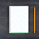 Blank lined notebook with pencil on chalkboard Stock Photos