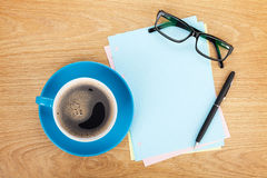 Blank lined paper with coffee, office supplies and glasses. On wooden table. Above view Royalty Free Stock Photography
