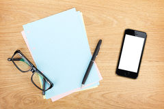 Blank lined paper with mobile phone, office supplies and glasses. On wooden table. Above view stock image