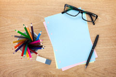 Blank lined paper with office supplies and glasses. On wooden table. Above view Stock Photo