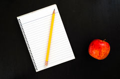 Blank lined paper page of notepad with yellow pencil on dark wooden desk with red apple Stock Photography