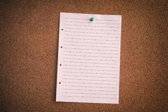 Blank lined paper sheet on bulletin board. Close up stock photo