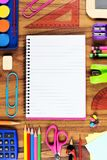 Blank lined school notebook with school supply frame over wood Royalty Free Stock Images