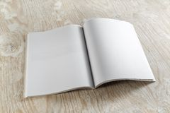 Blank magazine. Blank opened magazine on light wooden background with soft shadows. For design presentations and portfolios Royalty Free Stock Photography