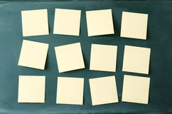 Blank many sticky notes attached to blackboard. Royalty Free Stock Images