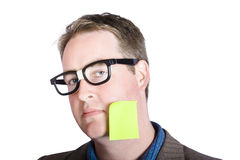 Blank marketing manager seeking inspiration idea. Absent minded male marketing manager seeking inspiration with blank page memo stuck to head over white Royalty Free Stock Image