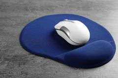 Blank mat and wireless mouse. On textured background Stock Photography