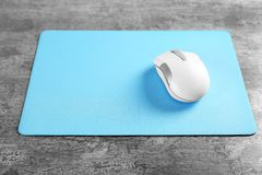 Blank mat and wireless mouse. On textured background Royalty Free Stock Image