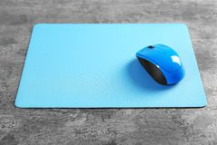 Blank mat and wireless mouse. On textured background Stock Photos