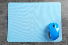 Blank mat and wireless mouse. On textured background Royalty Free Stock Photography