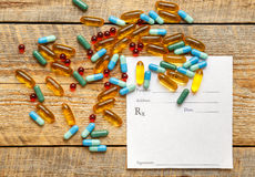 Blank medical prescription and pills on wooden table.  Stock Photography