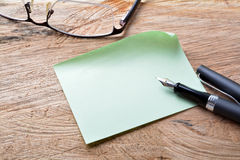 Blank memo with fountain pen. And glasses on wooden background royalty free stock photo