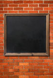 Blank menu blackboard on a brick wall. royalty free stock images