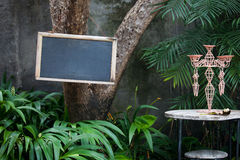 Blank menu Board on the tree in the garden restaurant or cafe. In a beautiful interior with a candlestick on the table and tropical leaves Royalty Free Stock Image