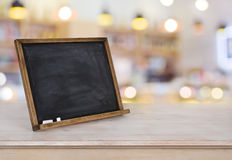 Blank menu board on wooden table over blurred restaurant background Royalty Free Stock Photo