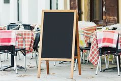 Blank menu chalkboard mockup on the street. With empty cafe seats Royalty Free Stock Images