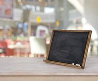 Blank menu chalkboard on wooden table over defocused cafe background.  Royalty Free Stock Photos