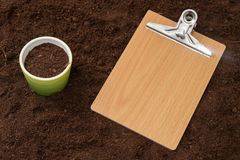 Blank message board and flowerpot on the soil.  royalty free stock image
