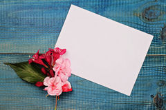 Blank message card and bouquet of flowers on blue wooden rustic table. Love, romantic, concept . Copy space background Royalty Free Stock Photos