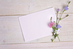 Blank message card and bouquet of flowers on white wooden table. Hipster, Rustic chic style. Retro, vintage image. Soft, pastel, g Stock Photos