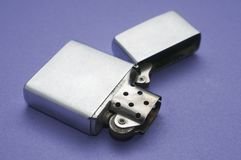 Blank metal lighter open on a purple table stock image