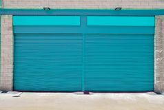 Closed store with pitch blind. A blank metal shutter door, with space for text, on a modern urban commercial shop at outdoors Royalty Free Stock Photo