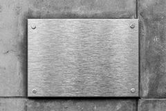 Blank metal sign or nameboard on concrete wall Stock Photography